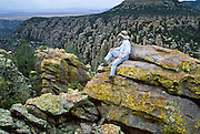 A hiker rests on a hoodoo at Chiricahua National Monument, Arizona, USA. The Heart of the Rocks Loop Trail (7 to 9 miles) makes an excellent day hike through fascinating arrays of hoodoos. 27 million years ago, huge volcanic eruptions laid down 2000 feet of ash and pumice which fused into rhyolitic tuff. This rock has eroded into fascinating hoodoos, spires, and balanced rocks which lie above the surrounding desert grasslands at elevations between 5100 and 7800 feet. At Chiricahua, the Sonoran desert meets the Chihuahuan desert, and the Rocky Mountains meet Mexico's Sierra Madre, making one of the most biologically diverse areas in the northern hemisphere. While we drove the dirt road to nearby Portal, Arizona, Carol saw a mountain lion crossing the road! Other animals here include javelina, coatimundi, bears, skunks, and deer.