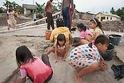 The hidden side of high tech smartphones. Miners -among them children of 10 years - sifting sand, the tin ore they find is kept in buckets.  The youngest children play beside the working adults, learning the mining skills. The entire Batako village works in the dangerous illegal mine, mere meters away from their homes. Illegal tin mine in Batako, Tunghin. Bangka Island (Indonesia) is devastated by illegal tin mines. The demand for tin has increased due to its use in smart phones and tablets.<br /> <br /> Le côté caché du succès des smartphones. Mineurs-dont des enfants de 10 ans - tamisent du sable, le minerai d'étain trouvé est conservé dans des seaux. Les jeunes enfants jouent à côté des adultes qui travaillent, et apprennent ainsi des techniques minières. Tout le village de Batako travaille dans la mine illégale et dangereuse, à quelques mètres de leurs maisons. L'île de Bangka (Indonésie) est dévastée par des mines d'étain sauvages. La demande de l'étain a explosé à cause de son utilisation dans les smartphones et tablettes.