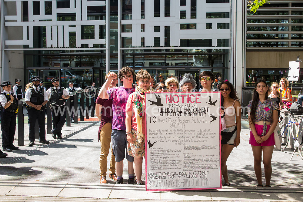 London, UK. 29 July, 2019. Activists from Reclaim the Power, All African Women's Group, Docs Not Cops, Lesbians and Gays Support the Migrants and other groups stand with a Notice to Cease and Desist with the Hostile Environment during a protest outside the Home Office to demand an end to the Government's 'hostile environment' policies.