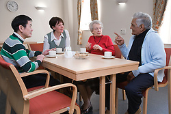 Group of older people and carer having tea in a care home,