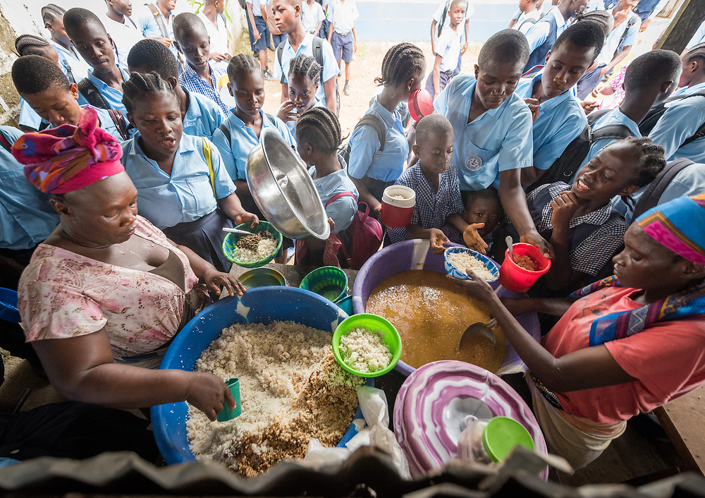 4 November 2019, Montserrado, Liberia: Students gather to receive a hot meal during recess. Started as a school for internally displaced children during the First Liberian Civil War, Mother Tegeste Stewart Apostolic Pentecostal Mission School in Montserrado county currently teaches 486 students from kindergarten up through 12th grade.