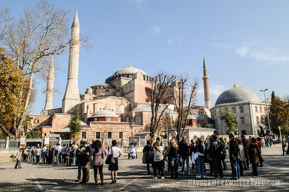 Tourists gather outside Hagia Sophia. Originally built as a Christian cathedral, then converted to a Muslim mosque in the 15th century, and now a museum (since 1935), the Hagia Sophia is one of the oldest and grandest buildings in Istanbul. For a thousand years, it was the largest cathedral in the world and is regarded as the crowning achievemen of Byzantine architecture.
