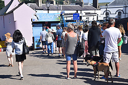 Holidaymakers queueing to buy boat trip tickets to Caldey Island, Tenby, Pembrokeshire South Wales July 2021