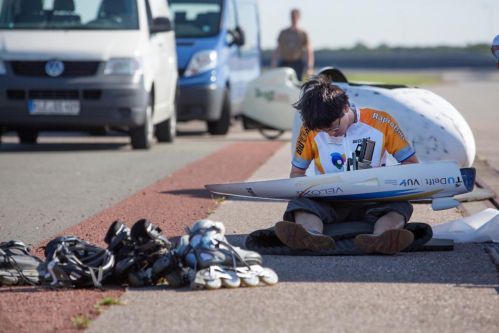 Eduard wertk aan de monitoren van de VeloX2. Het Human Power Team Delft en Amsterdam, bestaande uit studenten van de TU Delft en de VU Amsterdam, trainen op de RDW baan in Lelystad voor de laatste keer voor de recordpoging. In september wil het team met Jan Bos en Sebastiaan Bowier het snelheidsrecord op de fiets te verbreken. Dat record staat nu op 133 km/h.<br /> <br /> Eduard is preparing the canopy. Human Power Team Delft and Amsterdam are having the last training for the record attempt in Battle Mountain (USA) at the RDW test track in Lelystad. The team will try to break the world speed record with a human powered vehicle with riders Jan Bos and Sebastiaan Bowier. The record is now at 133 km/h..