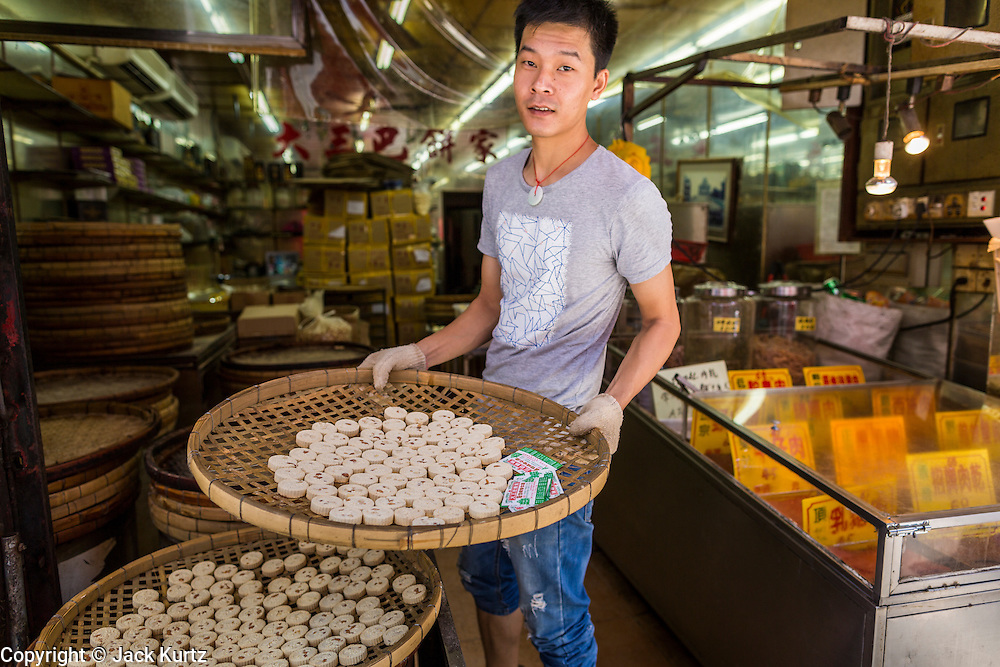 12 AUGUST 2013 - MACAU: A worker sets out almond cookies to cool in a bakery in Macau. Macau, also spelled Macao, is one of the two special administrative regions of the People's Republic of China (PRC), the other being Hong Kong. Macau lies on the western side of the Pearl River Delta across from Hong Kong to the east, bordered by Guangdong province to the north and facing the South China Sea to the east and south. The territory's economy is heavily dependent on gambling and tourism, but also includes manufacturing.     PHOTO BY JACK KURTZ