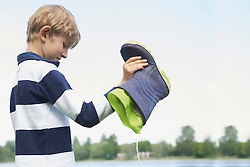 Boy pouring water out of a rubber boot, Bavaria, Germany