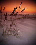 The sunset makes the sky glow orange and red behind sea grass lined sand dunes