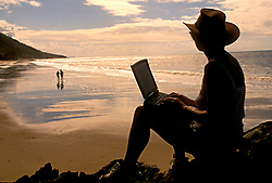 Stock photo of the silhouette of a woman on her laptop computer on the beach in the early evening