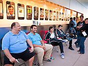 14 OCTOBER 2011 - SCOTTSDALE, AZ:   People wait in line under a display for iPhones at the Apple Store in Scottsdale Quarter to buy the new iPhone 4S. Hundreds of people lined up at the Apple Store in the Scottsdale Quarter in Scottsdale, AZ, Friday, Oct. 14, to buy the iPhone 4S. The phone sold out in pre-orders last week and sales at the Scottsdale Apple Store were brisk through the morning.     PHOTO BY JACK KURTZ