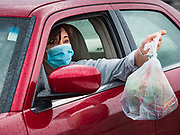 "11 APRIL 2020 - DES MOINES, IOWA: A motorist picks a ready to cook pasta meal during a food distribution in Des Moines. Most non-essential businesses in Iowa are closed until 30 April. Because of business closings causes by the Novel Coronavirus (SARS-CoV-2) pandemic, well over 100,000 Iowans filed first time claims for unemployment in the last three weeks, more than applied during the peak of the Great Recession of 2008. Local food banks have seen an unprecedented spike in people seeking nutritional assistance. Midwest Foods, a Des Moines based company and owner of Ginos Fine Italian Foods, gave away 1,000 complete dinners with sauce, noodles, salad, and dressing Saturday morning. People started lining up 3 hours before the food distribution began. The food distribution was done following ""social distancing"" guidelines and all of the workers wore masks and gloves.       PHOTO BY JACK KURTZ"