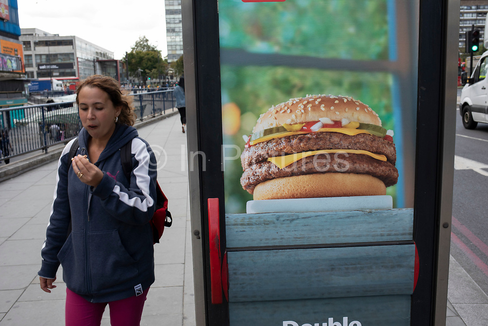Woman eating a burger while passing an advertisement for burgers at Elephant and Castle in London, UK. The area is now subject to a master-planned redevelopment budgeted at £1.5 billion. A Development Framework was approved by Southwark Council in 2004. It covers 170 acres and envisages restoring the Elephant to the role of major urban hub for inner South London.