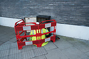 Telecoms workman cordoned off as he works on a telephone exchange box. London, England, UK.