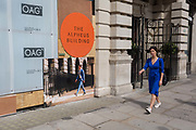 A lady wearing a distinctive blue dress walks past a board showing a man wearing a similar colour shade at the Alpheus Building on Blomfield Street, a property being refurbished near Liverpool Street Station in the City of London, the capitals financial district - aka the Square Mile, on 8th August, in London, England. The address at 31–35 Blomfield Street is a modern retail space behind a historic Edwardian facade.