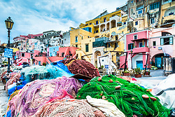Colorful Italian fishing port, Procida Italy.  I love the fishing villages of Italy because of their vivid color and buildings from antiquity. <br /> <br /> What caught my eye here was although the fishing nets appear to be a jumbled mess, they are all a different colors so the individual fishermen who live in the abodes above can tell which net is theirs; organized colorful chaos.