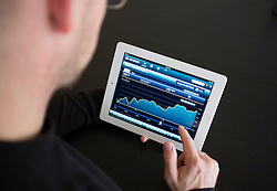 Man checking performance of Dow Jones stock market prices on iPad3 tablet computer