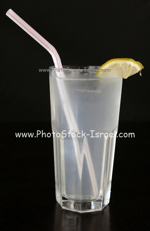 Cool refreshing lemonade drink with a straw and a lemon slice on black background