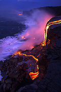 Pahoehoe flows over an existing sea cliff at Kupapa'u, creating a new delta below as it enters the ocean.  Glow radiating from the lava reflects off the rising steam plume in subtle pastel shades.