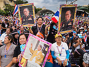 """15 NOVEMBER 2013 - BANGKOK, THAILAND:  Thai royalists wave photos of Bhumibol Adulyadej, the King of Thailand, during a anti-government protest in Bangkok. Thai royalists accuse the government of Prime Minister Yingluck Shinawatra of not being supportive enough of the monarchy. Tens of thousands of Thais packed the area around Democracy Monument in the old part of Bangkok Friday night to protest against efforts by the ruling Pheu Thai party to pass an amnesty bill that could lead to the return of former Prime Minister Thaksin Shinawatra. Protest leader and former Deputy Prime Minister Suthep Thaugsuban announced an all-out drive to eradicate the """"Thaksin regime."""" The protest Friday was the biggest since the amnesty bill issue percolated back into the public consciousness. The anti-government protesters have vowed to continue their protests even though the Thai Senate voted down the bill, thus killing it for at least six months.     PHOTO BY JACK KURTZ"""