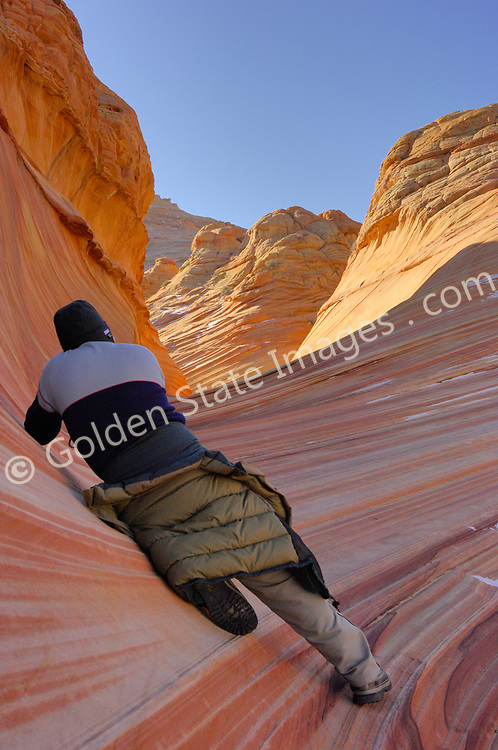 """Paria Canyon - Vermillion Cliffs Wilderness area in Southern Utah.<br /> <br /> Coyote Buttes North located in the Paria Canyon - Vermilion Cliffs Wilderness. This area features one of the most well-known geologic sandstone formations in the world, called """"The Wave"""".<br /> <br /> The Wave is a spectacular area of sandstone formations twisted into the shapes of breaking waves pillars cones and mushrooms.<br /> <br /> An ancient sea laid down layers of sediment deposits which hardened to form the multicolored sandstone rock. Over eons the actions of water the cycles of baking heat and subfreezing temperatures and wind have formed its complex undulating shapes.<br /> <br /> The deep reds of the rock and their shapes appear to change with the seasons and time of day."""