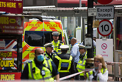 © Licensed to London News Pictures.  10/08/2021. London, UK. Police guard a scene after a women in her 30s has been killed after a collision involving two buses and three pedestrians outside Victoria Station, central London. The woman was pronounced dead at the scene at 9am.  Photo credit: Marcin Nowak/LNP