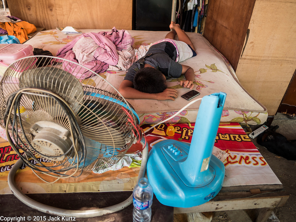 01 JULY 2015 - THA CHAI, CHAI NAT, THAILAND: A boy sleeps on a bed in recovered from his home after it slid into the Chao Phraya River in Chai Nat province. The riverbank collapsed because the water level is low. Six homes, with 23 people living in them, slid into the river. No one was hurt. Central Thailand is contending with drought. By one estimate, about 80 percent of Thailand's agricultural land is in drought like conditions and farmers have been told to stop planting new acreage of rice, the area's principal cash crop. Water in reservoirs are below 10 percent of their capacity, a record low. Water in some reservoirs is so low, water no longer flows through the slipways and instead has to be pumped out of the reservoir into irrigation canals. Farmers who have planted their rice crops are pumping water out of the irrigation canals in effort to save their crops. Homes have collapsed in some communities on the Chao Phraya River, the main water source for central Thailand, because water levels are so low the now exposed embankment is collapsing. This is normally the start of the rainy season, but so far there hasn't been any significant rain.     PHOTO BY JACK KURTZ