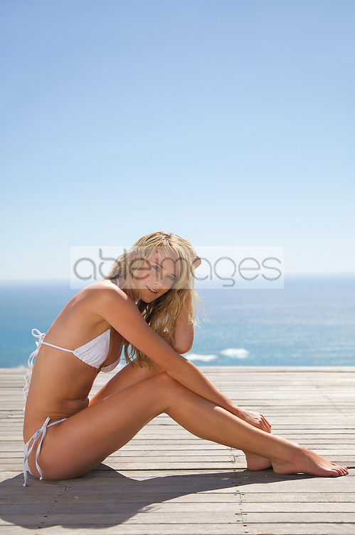 Young woman sunbathing with ocean in the background