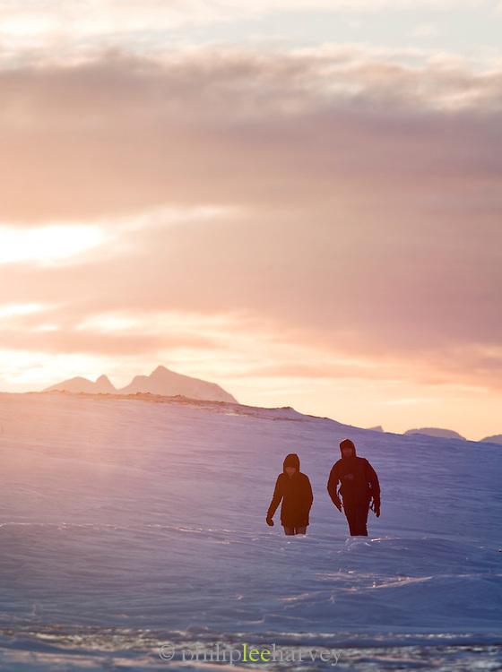 Tourists walk through the deep snow on the top of Mount Storsteinen, Tromso, Norway