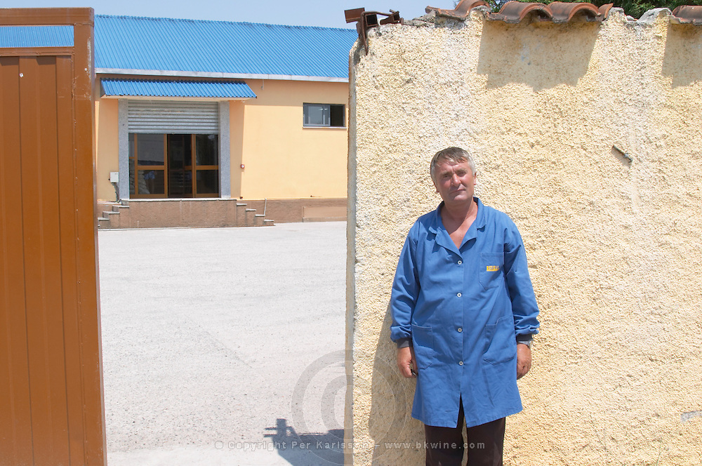 The winery with a winery worker standing next to the gate. Kantina Miqesia or Medaur winery, Koplik. Albania, Balkan, Europe.