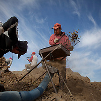 """Purevsuren, left, and Dondog Tumur-chudur, in red, operate a simple sifting machine that separates smaller particulate from larger rocks at a gold mining site in Uyanga soum, Mongolia. """"If I don't find anything, I'll have nothing to eat,"""" says Dondog Tumurchudur, a herder-turned-miner. """"I can't make enough money from herding."""""""
