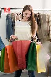 Young woman holding shopping bags, smiling
