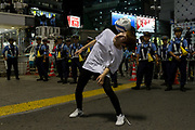 A Japanese soccer fan shows off his ball juggling skills in front of a line of police before fans  celebrate the Japan National Team qualifying for the next round of the 2018 World Cup in Russia. Japan lost to Poland  0-1 but managed to move to the next stage on points. Thousands of younger fans gathered at Tokyo's iconic Shibuya crossing to enjoy the moment with police controlling the crowds