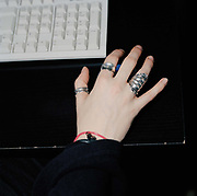Detail of a female office worker, at a call centre in kingston, May 2006;  the worker is expressing her identity primarily with her bold jewellery.  From the series Desk Job, a project which explores globalisation through office life around the World.
