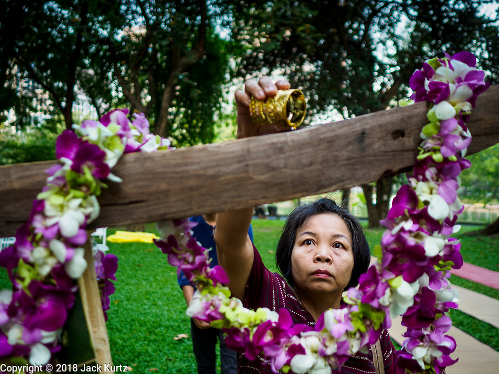 """17 MARCH 2018 - BANGKOK, THAILAND:  A woman pours floral water into an altar in Lumpini Park during a """"sticky rice merit making"""" in the park in Bangkok. Sticky rice merit making is a merit making in the Isan / Lao style, when people present small amounts of cooked sticky rice (also known as glutinous rice) to Buddhist monks. Isan is the northeast region of Thailand.    PHOTO BY JACK KURTZ"""