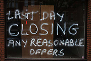 Sprayed writing on a closed recession business window. The words 'Last Day Closing .. any reasonable offers'. Around a recession-bled Britain, high-street businesses have been going bust in their thousands. Britain has now endured eight recessions since the Second World War. No two recessions are alike, and that applies to the current slowdown also. It has been caused by a shock to the availability of credit, a massive build up of debt. The number of people out of work currently stands at almost two million. Given the rate at which the economy is deteriorating this could easily be above three million. From a continuing piece of work about windows and urban messages, the picture is from the project of closed business windows: 'Bust - the Art of Recession'.