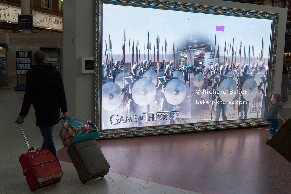 As a passenger with baggage walks past on his way to a platform, a young child watches a large screen showing an augmented reality world of the station concourse and fantasy creatures, part of a loop of ads for Visit Scotland and for HBO's Game of Thrones, in London, England, on 4th December 2019.