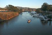 A boat travels upstream in the Napa River, in Napa, California, USA.