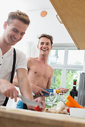 Homosexual couple cooking food in kitchen, smiling