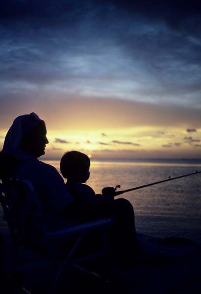Stock photo of the silhouette of an adult and child fishing from a pier at sunset