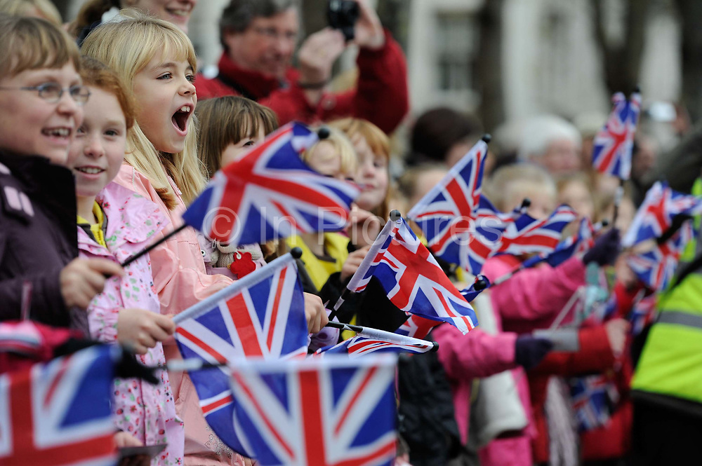 Young girls wave union jack flags at the traditional Lord Mayor's parade through London.