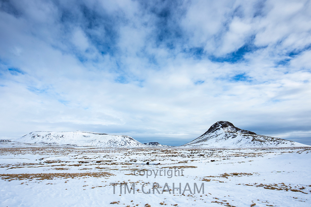 Puffy clouds over typical Icelandic winter landscape of mountain and volcanic lava mound in South Iceland