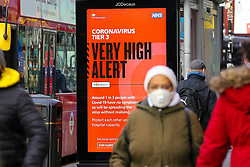 © Licensed to London News Pictures. 19/12/2020. London, UK. A woman wearing a face covering in north London walks past the government's 'Very High Alert Level' publicity campaign poster amid fears of a Christmas lockdown as infection rates rise. Prime Minister Boris Johnson will hold a press conference later today after meeting with ministers, where it is understood they discussed a possible ban on commuters entering London and travel to and from the South East. Photo credit: Dinendra Haria/LNP