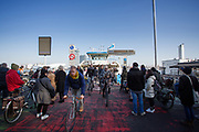 In Amsterdam verlaten fietsers en voetgangers het pontje over het IJ, terwijl een nieuwe groep passagiers al staat te wachten.<br /> <br /> In Amsterdam cyclists and pedestrians are leaving the ferry across the IJ, while a new group of passengers is waiting to enter.