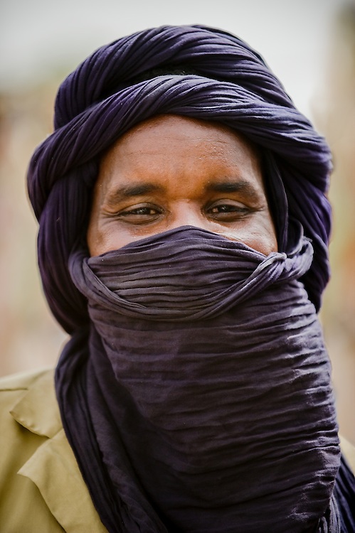 Portrait of a young Fulani man wearing a dark purple head dress in northern Burkina Faso. The Fulani or Peul are nomadic herdsmen of the Sahel region of West Africa.