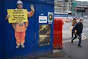 Cutout workman at the Crossrail development site at Tottenham Court Road, holding up a sign saying that businesses are open for business as usual. Including the nightclub GAY. London, UK.