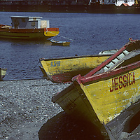 Puerto Montt, Chile.  Fishing boats float in the harbor and rest on a beach at Puerto Montt, in the Lakes District of Patagonia.