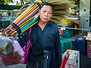 01 DECEMBER 2016 0 BANGKOK, THAILAND: A broom vendor walks through the traditional market on Lan Luang Road in Bangkok. The market is on the site of one of the first western style cinemas in Bangkok. The movie theatre closed years ago and is still empty but the market fills the streets around the theatre.     PHOTO BY JACK KURTZ
