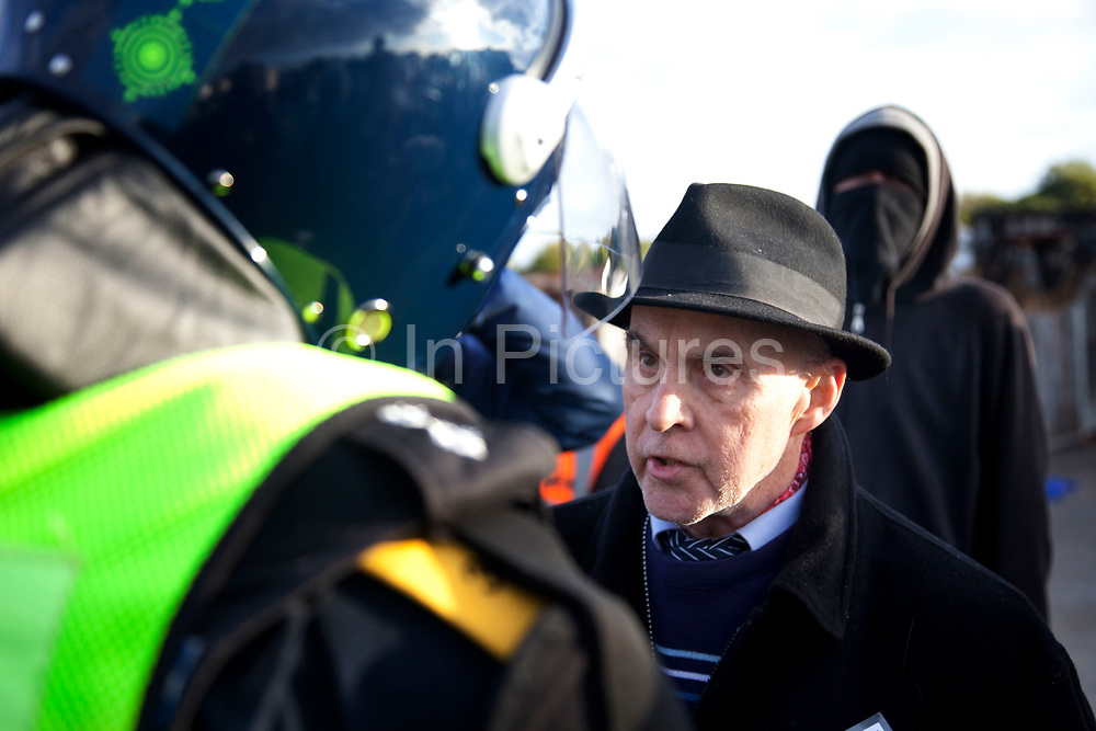 Spokesperson for the travellers Grattan Puxon talks to a riot policeman. Travellers at Dale Farm site prior to eviction. Riot police and bailiffs were present on 20th October 2011, as the site was cleared of the last protesters chained to barricades. Dale Farm is part of a Romany Gypsy and Irish Traveller site in Crays Hill, Essex, UK<br /> <br /> Dale Farm housed over 1,000 people, the largest Traveller concentration in the UK. The whole of the site is owned by residents and is located within the Green Belt. It is in two parts: in one, residents constructed buildings with planning permission to do so; in the other, residents were refused planning permission due to the green belt policy, and built on the site anyway.