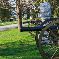 Gettysburg, PA, USA / March 23, 2012: Civil war cannons near soldiers' graves in the Gettysburg National Cemetery.