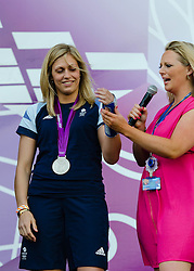 © Licensed to London News Pictures. 04/08/2012. London, UK. Gemma Gibbons and Karina Bryant of the Team GB Judo squad onstage at BT London Live, Hyde Park, to celebrate their medal winning success.  Gemma won the silver medal in the women's under-78kg's, and Karina won the Bronze in the women's over-78kg's.  In this pic - Gemma achieved her success despite a broken thumb, which she shows here.  Photo credit : Richard Isaac/LNP