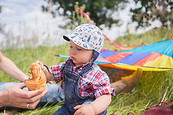 Father giving croissant to his little baby boy on meadow in the countryside, Bavaria, Germany